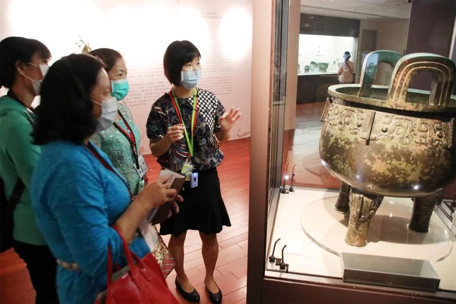 印尼新住民吳曉雯(右1)介紹商朝青銅食器「祖己鼎」,用生動的方式解說。(移民署提供/李文正台北傳真)