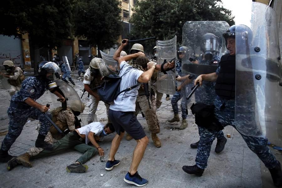 黎巴嫩大爆炸造成158人喪命、逾6,000人受傷,不滿政府貪腐、無能,導致悲劇發生,近萬黎巴嫩民眾8日走上街頭,抗議行動演變為激烈警民衝突,民眾攻陷外交部、銀行協會等政府部會,警方對群眾發射催淚瓦斯、橡膠子彈,衝突造成1名警員喪命、逾2,000人受傷。(圖/美聯社)