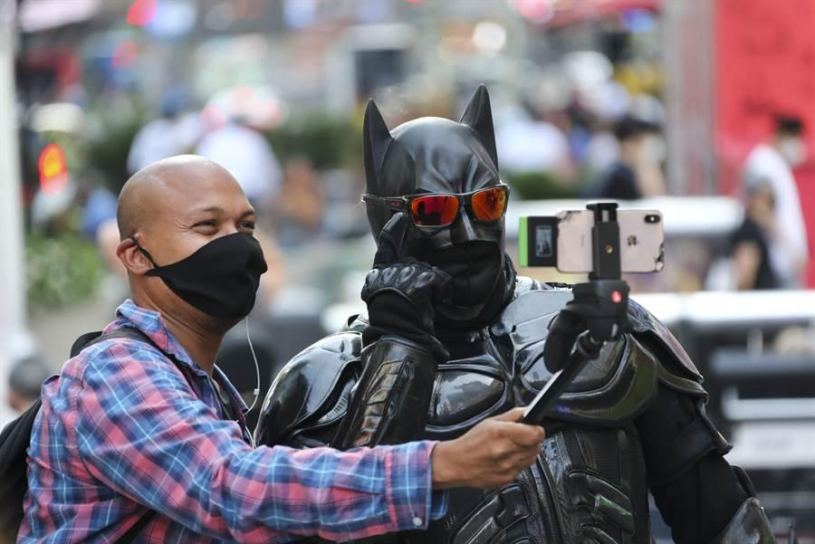 美國新冠確診病例9日突破500萬例,圖為紐約時報廣場,一名男子與裝扮成蝙蝠俠的演員合影。(新華社)