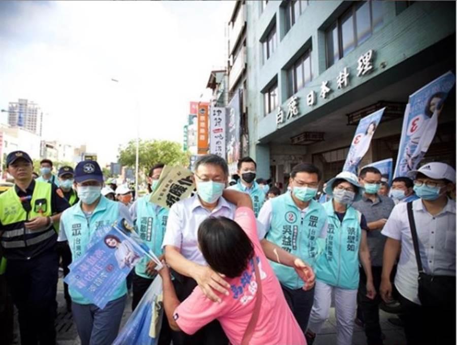 民眾黨主席柯文哲在IG上傳一張照片,他與手拿國民黨補選候選人李眉蓁旗子的藍粉擁抱。(翻攝柯文哲IG)