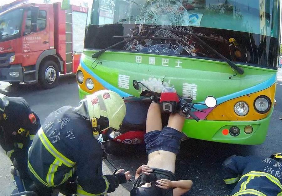 嘉義公車與機車對撞,女騎士雙腿插入車頭後翻空倒掛,驚險萬分。(嘉義市消防局提供)