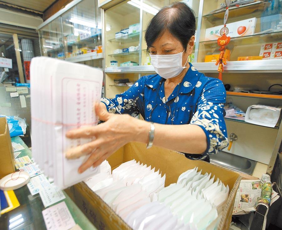 台灣本土疫情蠢動,口罩搶購潮再現,政府傳將擴大徵收口罩至總產量8成,必要時不排除全數徵用。圖為藥局人員整理口罩。(陳怡誠攝)