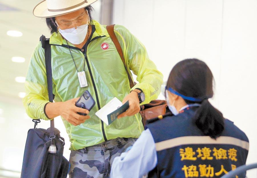 台灣本土疫情蠢動,口罩搶購潮再現,政府傳將擴大徵收口罩至總產量8成,必要時不排除全數徵用。圖為桃機入境旅客查驗健康聲明書。(范揚光攝)