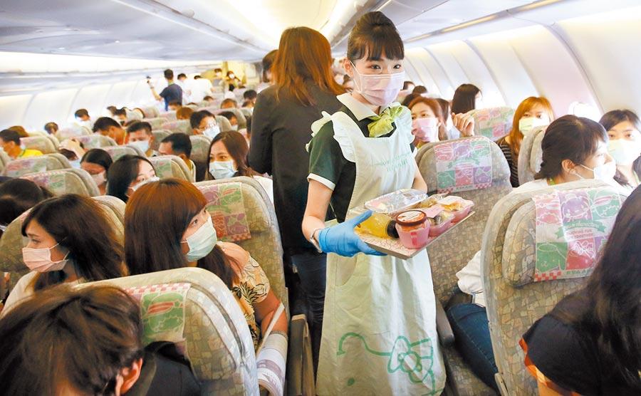 長榮航空類出國包機8日從桃園機場起飛,航程中空服員為旅客發送餐點。(范揚光攝)