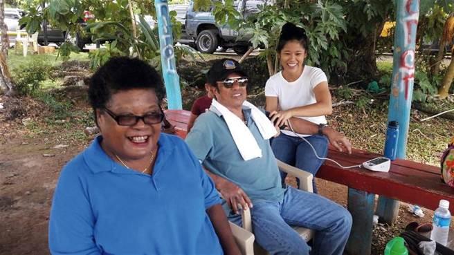 周語亭(右)為帛琉總統雷蒙傑索(中)量血壓。(周語亭提供)