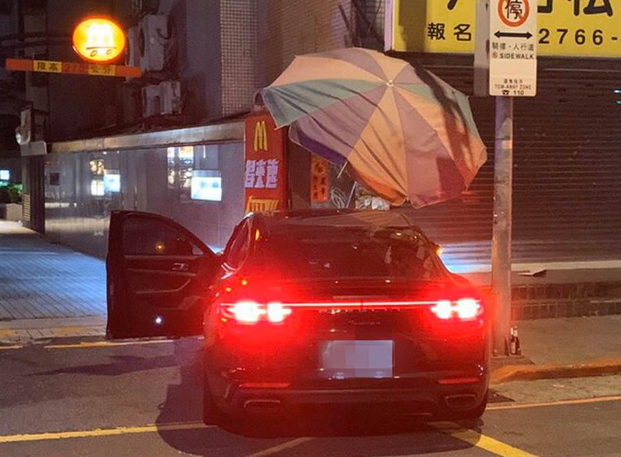 保時捷跑一頭撞上麥當勞得來速車道圍牆,遮陽傘也遭殃。(民眾提供/戴志揚翻攝)