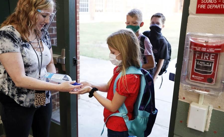 最新報告指出,才短短2周,美國就新增將近10萬名兒童確診,此外,喬治亞州一所高中上周復課,一張學生擠滿走廊、且多數人都未戴口罩的照片在網路上瘋傳,現在更傳出學校有9名師生確診,學校已緊急關閉。(資料照/美聯社)