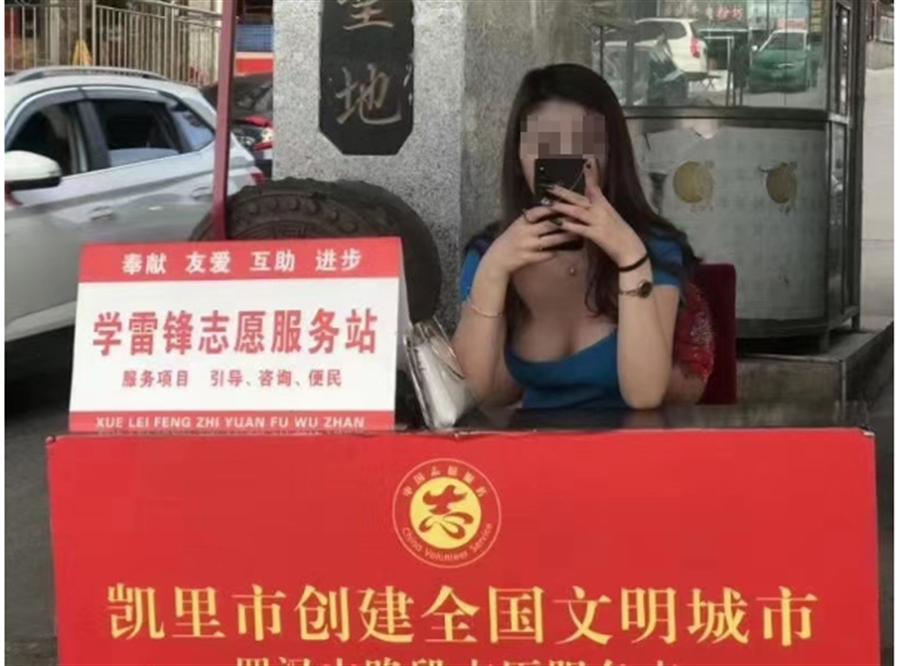 大陆贵州黔东南州凯里市里的一处「学雷锋志愿服务」,惊见2位穿着洋装的低胸巨乳正妹坐在摊位上,悠閒的滑着手机。(取自星岛网)