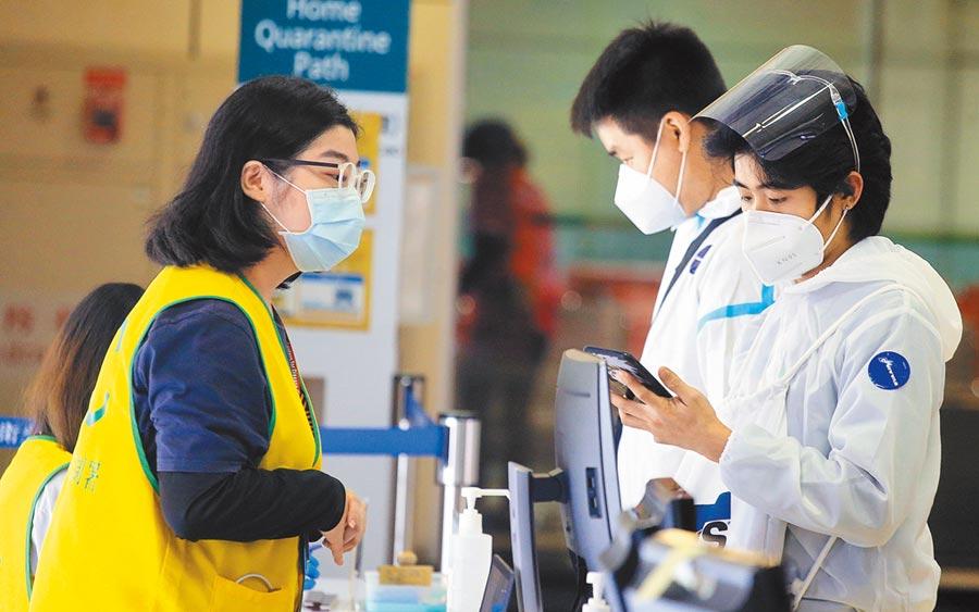 在桃園機場入境管制區內,2名身穿防護衣、從菲國搭機抵台的旅客,正在查驗健康聲明書。(范揚光攝)