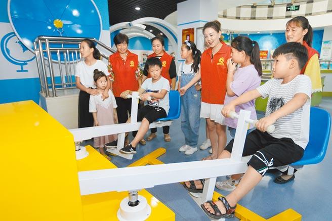 7月30日,志工帶領幾位兒童在安徽省淮北市科技館體驗「電磁翹翹板 」。(新華社)