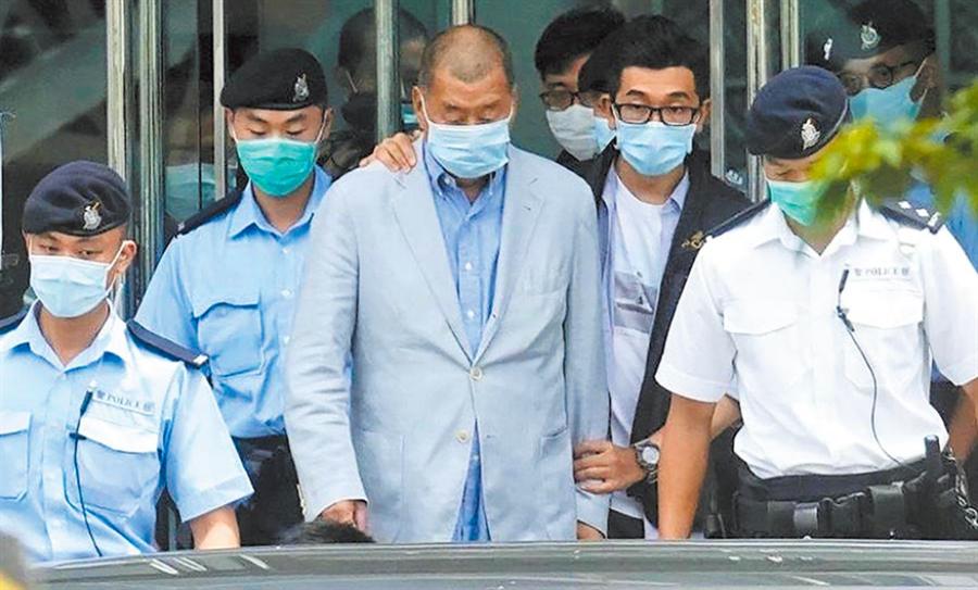 香港壹傳媒創辦人黎智英,昨被港警帶往香港《蘋果日報》總部大樓,協助調查。(美聯社)