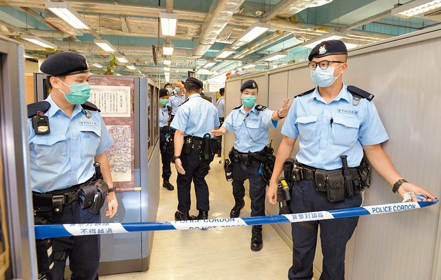 香港警方昨日搜查香港《蘋果日報》總部大樓,帶回25箱證物。(路透)