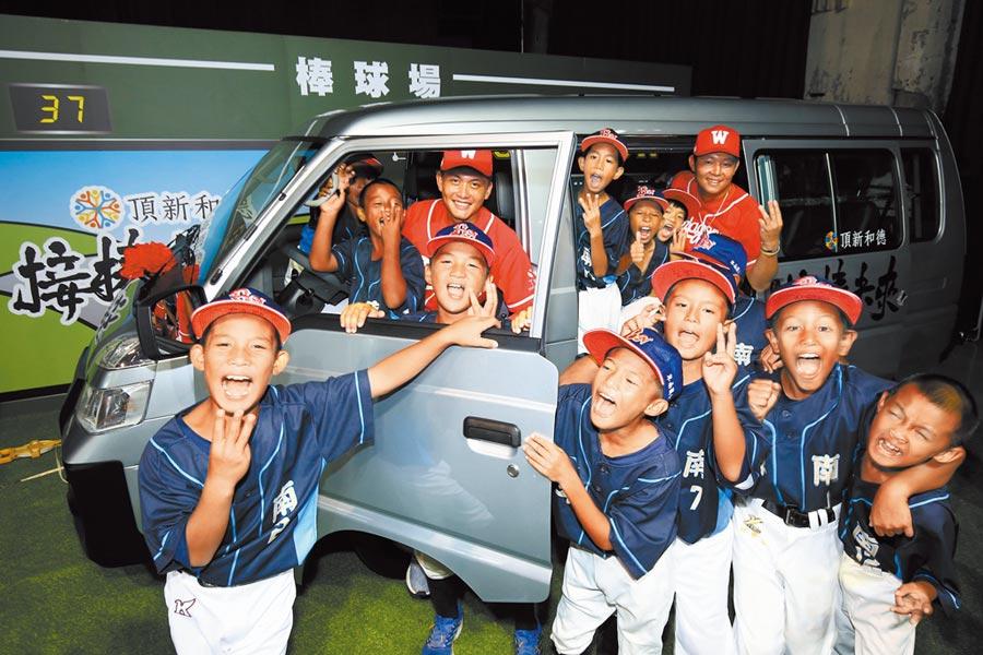 卑南國小少棒隊獲贈交通車,小球員與味全龍隊劉基鴻(紅衣左)、黃柏豪(紅衣右)開心合照。(頂新和德文教基金會提供)