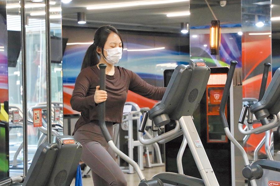 3月5日,部分浙江健身場館逐步復工,一位市民戴著口罩使用橢圓機鍛鍊。(中新社)