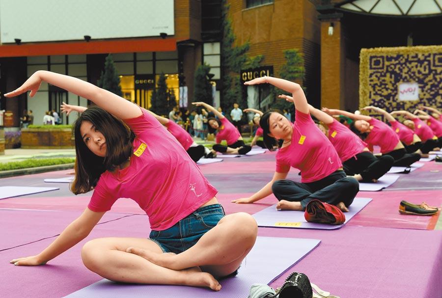 一場疫情改變人們運動習慣。圖為重慶辣媽坐在瑜伽墊上練瑜伽。(中新社)