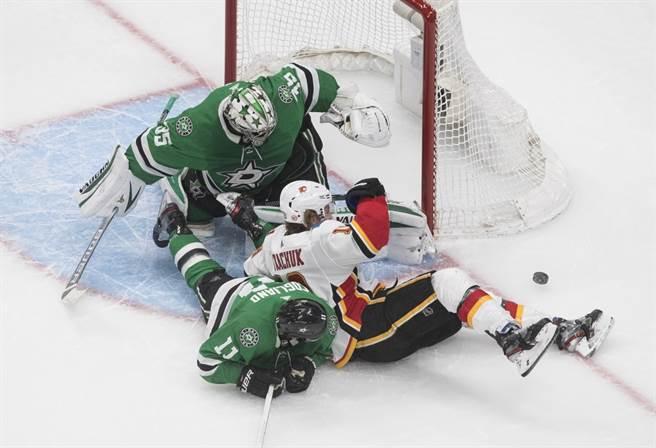 NHL卡加利火焰(白)與達拉斯星辰(綠)的球員在門前撞成一團。(美聯社資料照)