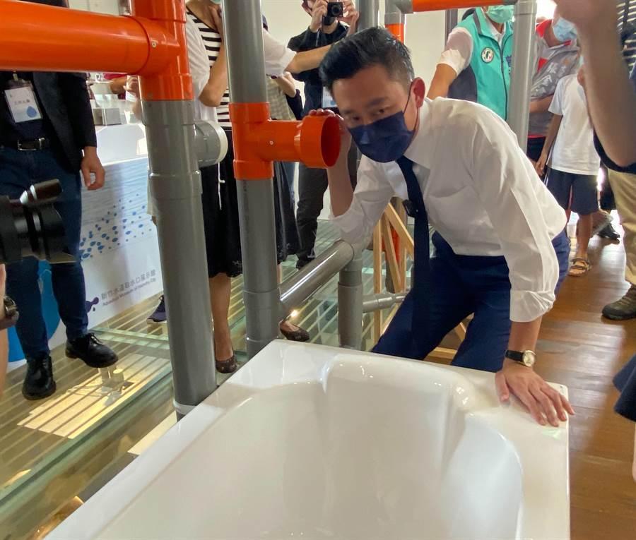 新竹市林智堅今天搶先進入新竹水道取水口展示館參觀體驗,聆聽像是水管等物件,感受水的流動。(陳育賢攝)