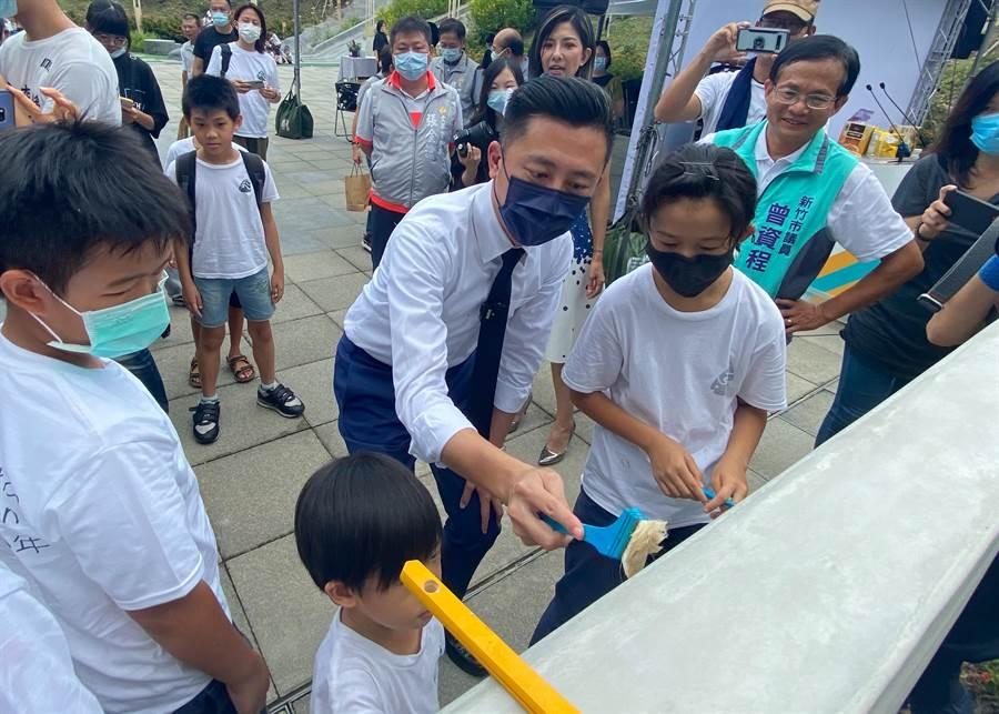 新竹市文化局即日起在新竹水道取水口推出「細水逐流─水資源環境教育展」,市長林智堅今天也跟孩子們一起在戶外水畫牆上畫出水滴狀圖案。(陳育賢攝)