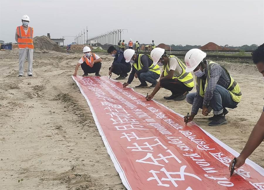 「一帶一路」上的抗疫前行,6月1日,在孟加拉國帕德瑪大橋鐵路連接線項目軌枕生產廠區,當地員工佩戴口罩參加安全生產月簽名活動。(新華社)