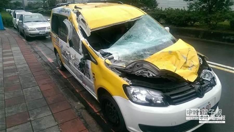 當時駕駛周錫東所駕駛的計程車,被機翼擊中撞爛的情景。(中時資料庫)