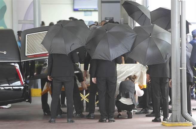 故總統李登輝移靈車隊14日抵達北市第二殯儀館,工作人員將其靈柩安置定位,準備推往火化。(張鎧乙攝)