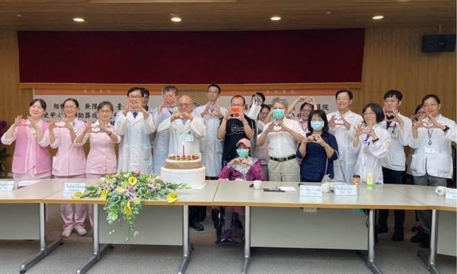 (40歲的趙小姐去年產後發生心臟衰竭,卻等不到移植心臟。今年6月置入心室輔助器幫助維持心臟功能,如今漸漸能下床復健,等待順利換心的那天。台大醫院團隊今為她準備蛋糕,慶祝其救治過程順利。圖片來源:羅真)