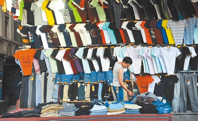 一名大陸顧客在新疆喀什夜市選購平價服飾。(新華社資料照片)