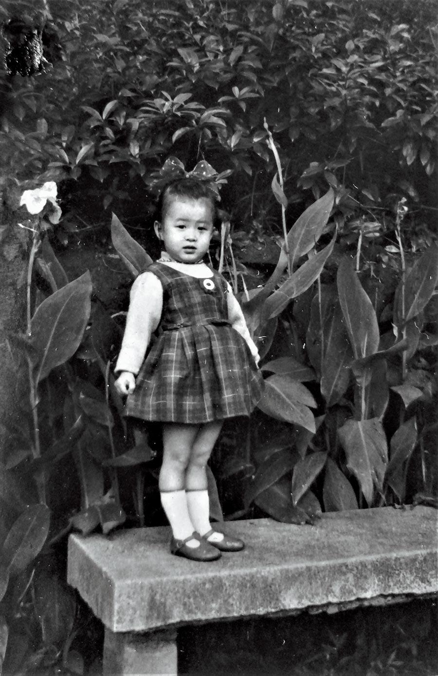 羅霈穎三歲時站在庭院美人蕉前。(羅青提供)
