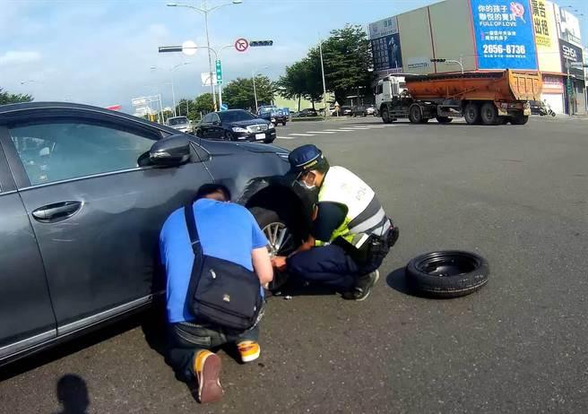 員警在馬路中央幫車輛換起備胎來,排除狀況後讓車主對警方敬佩不已。(民眾提供/盧金足台中傳真)