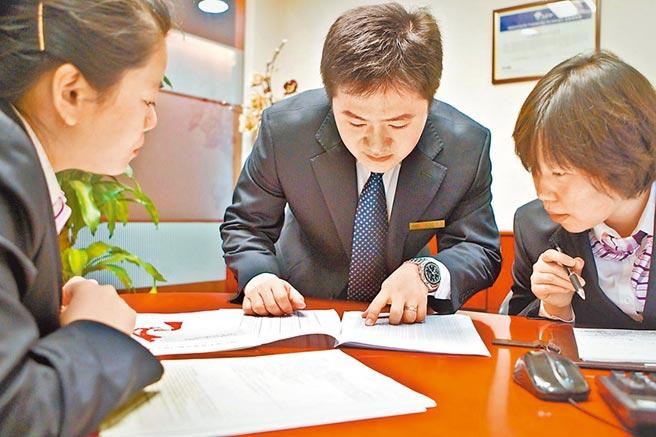 北京一家外資銀行的金融理財師與兩位同事交流業務。(新華社資料照片)