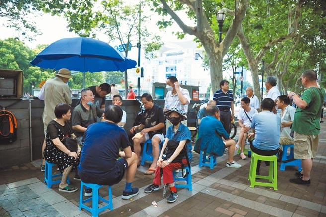 7起初A股開始上漲,上海市廣東路上的「股市沙龍」人氣火爆。每到周末,股民聚集在此交流市場走勢和個股信息。(中新社資料照片)