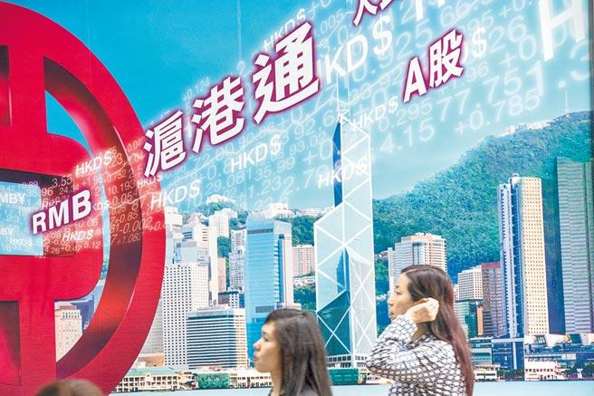 從香港流入大陸的外資被稱為北上資金。圖為香港市民從中環一家銀行的滬港通廣告牌前走過。(新華社資料照片)