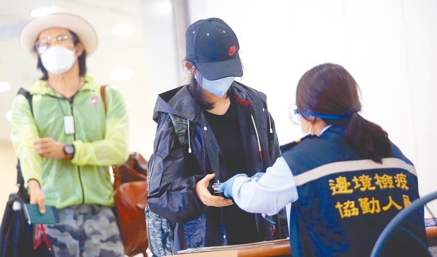 為旅客搭機抵達桃園機場,在入境前查驗健康聲明書。(范揚光攝)