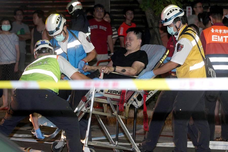 蔡姓屋主(中)被救出時臉上盡是痛苦表情,不斷向警消人員表示兒子仍在屋內。(黃世麒攝)