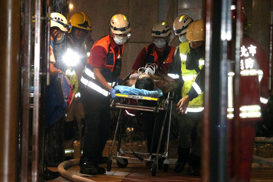 蔡姓屋主的兒子(躺在擔架者)被警消救出,輕微嗆傷,所幸沒有生命危險。(黃世麒攝)