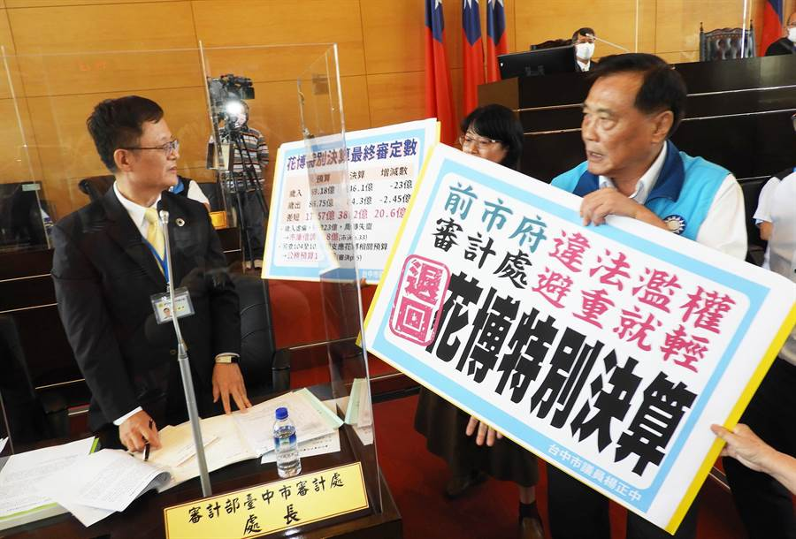 藍營市議員手持退回花博決算的看板,直接拿到吳錦祥(左)處長座位前,強烈表達退回花博決算的決心。(陳世宗攝)