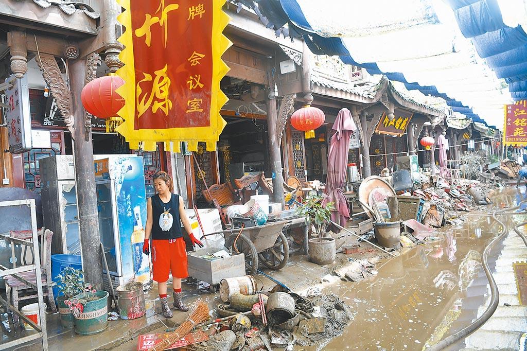 8月19日,成都黃龍溪古鎮洪水退去後,商戶開始清理淤泥。(中新社)