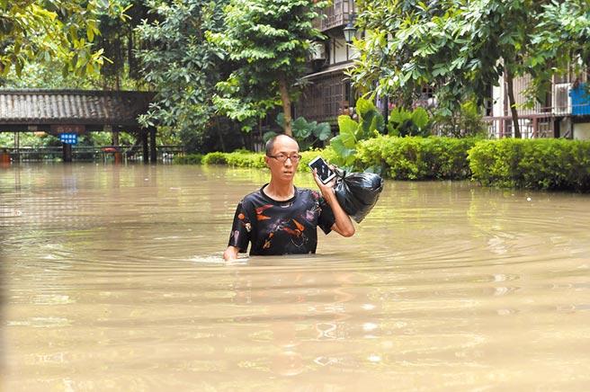 8月19日,重慶市沙坪壩區低窪路段大淹水,市民涉水出門。(中新社)