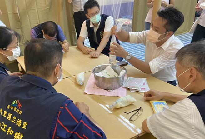 地震等天然災害,沒水、沒電,大里區立德里民在瓦愣紙桌上,實際演練如何用少許的溪水,使用救助用炊飯袋,煮食米飯。(江和樹提供/黃國峰台中傳真)