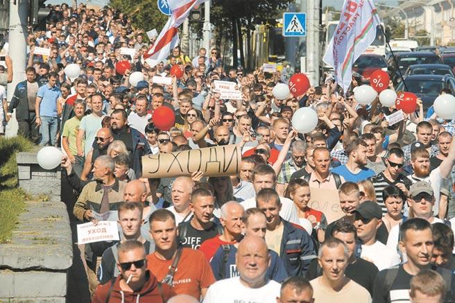滾蛋!白俄羅斯罷工工人舉起滾蛋的標語,要求到拖拉機工廠視察的總統盧卡申科下台。(美聯社)