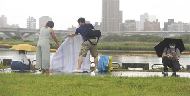 因應巴威颱風海警發布,台北市政府22日下午4點13分宣布,「2020大稻埕情人節」的舞台活動及煙火施放均延期辦理,後續將另行公告活動舉辦時間,一對情侶在風雨中收拾物品,離開活動現場。(張鎧乙攝)