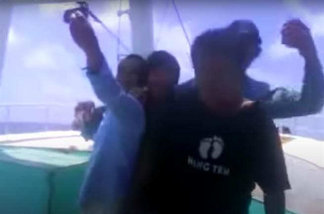 黑人男子遭擊斃後,船上外籍船員還開心合照。(取自Youtube/袁庭堯高雄傳真)