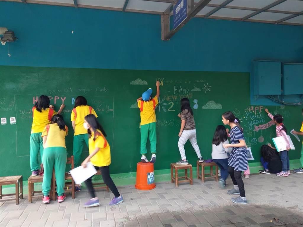 生態學校行動團隊鼓勵孩子們透過不同管道進行發表與擴散,影響更多人,圖為孩子們創作塗鴨牆來慶祝世界地球日。(曹婷婷攝)