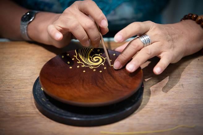 杨琇文将「漆线雕」应用在生漆涂制的木盘上,进行复合媒材创作。(袁庭尧摄)