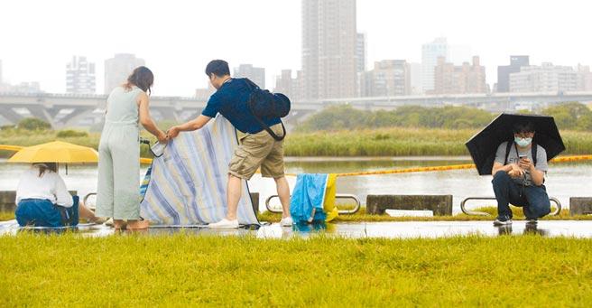 因應巴威颱風海警發布,台北市政府22日下午4點13分宣布,2020大稻埕情人節」的舞台活動及煙火施放均延期辦理,後續將另行公告活動舉辦時間,一對情侶在風雨中收拾物品,離開活動現場。(張鎧乙攝)