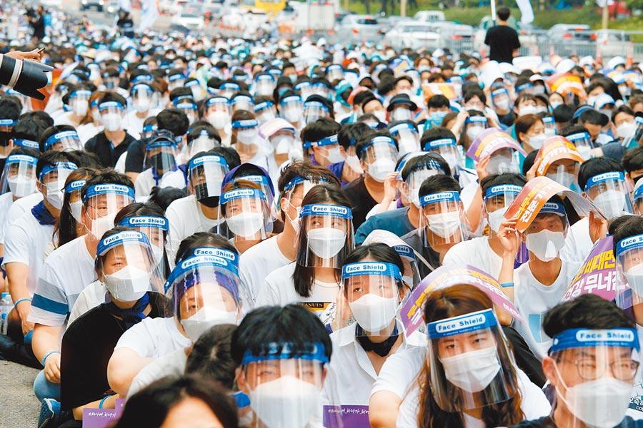 南韓醫護人員穿戴防護器具在首爾街頭示威,抗議政府計畫培訓更多醫學生。南韓預計未來10年增加4000名醫學生,為潛在的傳染病爆發作準備。南韓醫學會(KMA)宣稱,南韓醫生數量早已供過於求。(路透)