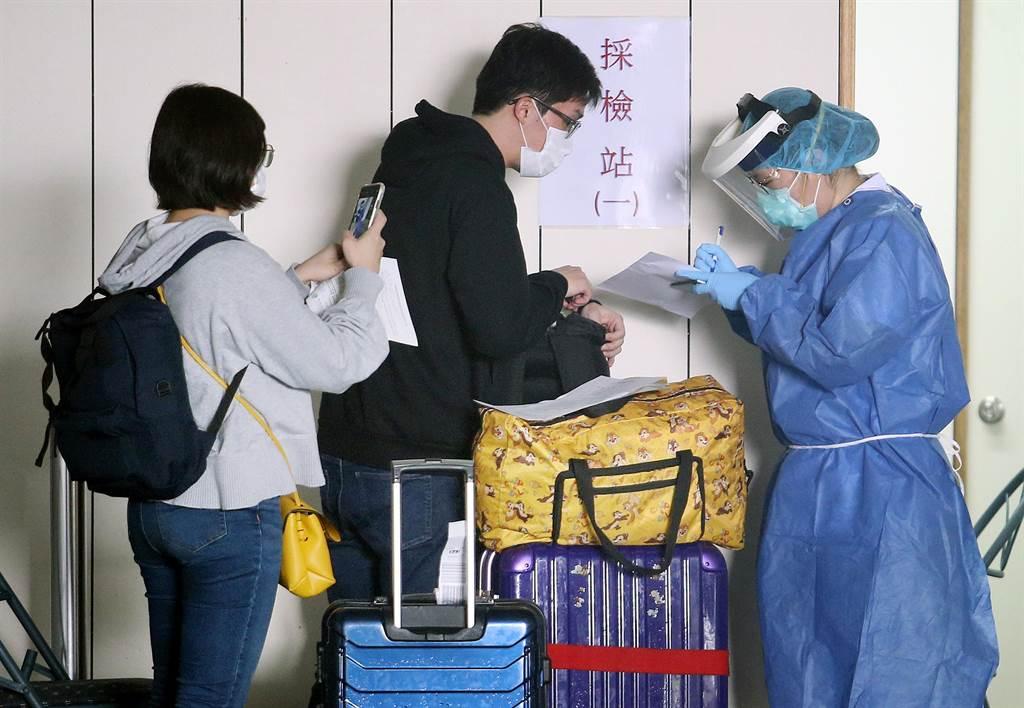 圖為在桃園機場第二航廈的採檢站中,2名剛入境的旅客正準備採集檢體。(資料照,范揚光攝)