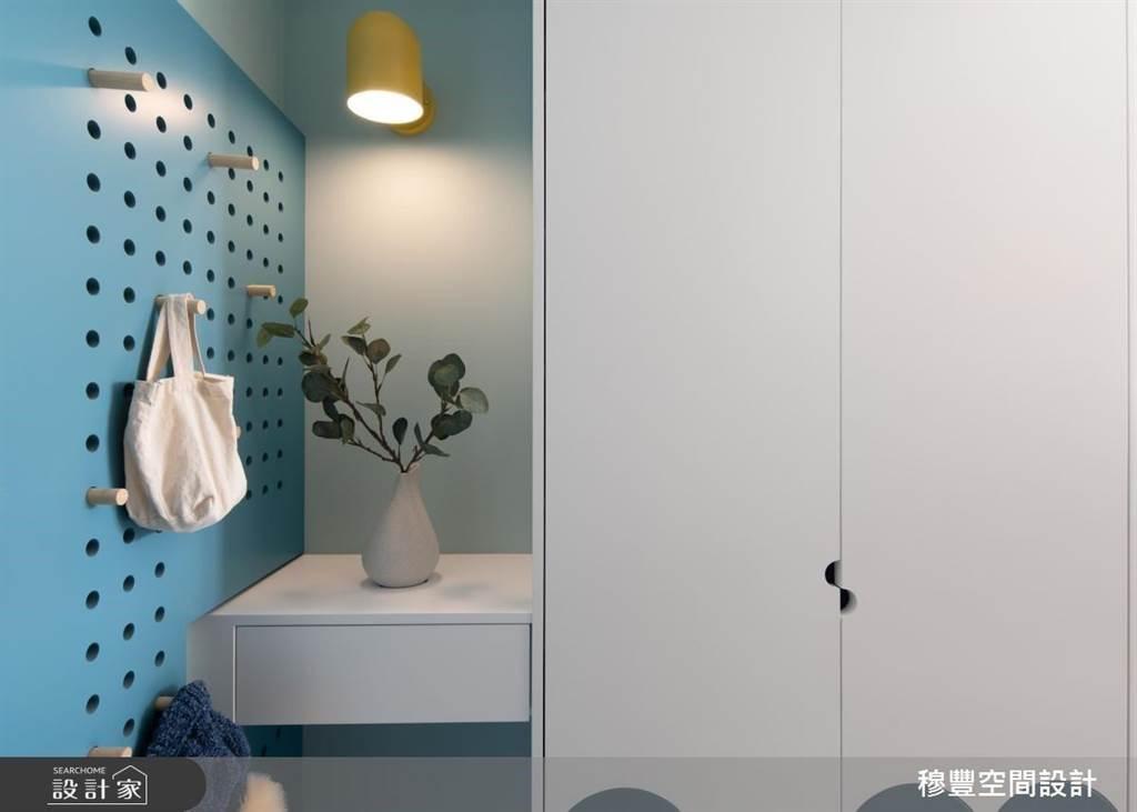 挑選天藍色的長型洞洞板與系統櫃搭配使用,能夠依照屋主的使用習慣用來吊掛包包手袋,連外套雨衣都可以直接懸掛晾乾。(圖片提供/穆豐空間設計)