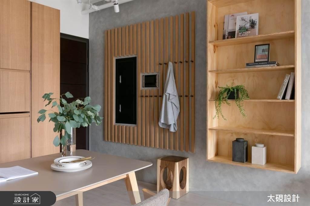利用木格柵做出貼壁的吊掛收納,修飾家中破壞美感的電箱,鞋櫃則與餐櫃整合在一起,加上一張小椅凳,16坪小宅也可以有特色玄關。(圖片提供/太硯設計)