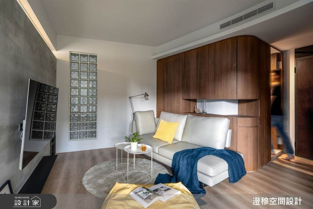 僅有10坪大的套房用一座木作櫃體將玄關鞋櫃、沙發背牆整合在一起,也讓位於門口的衛浴被巧妙地隱藏起來。(圖片提供/澄穆空間設計)